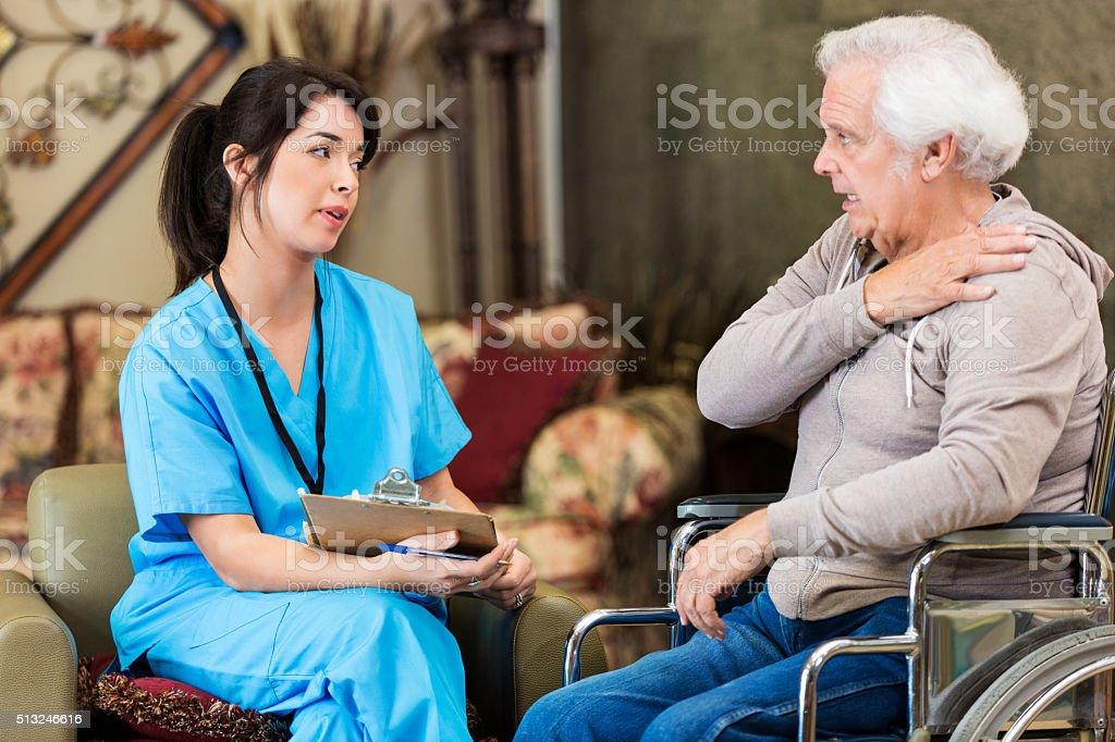 Senior man explains symptoms to nurse stock photo
