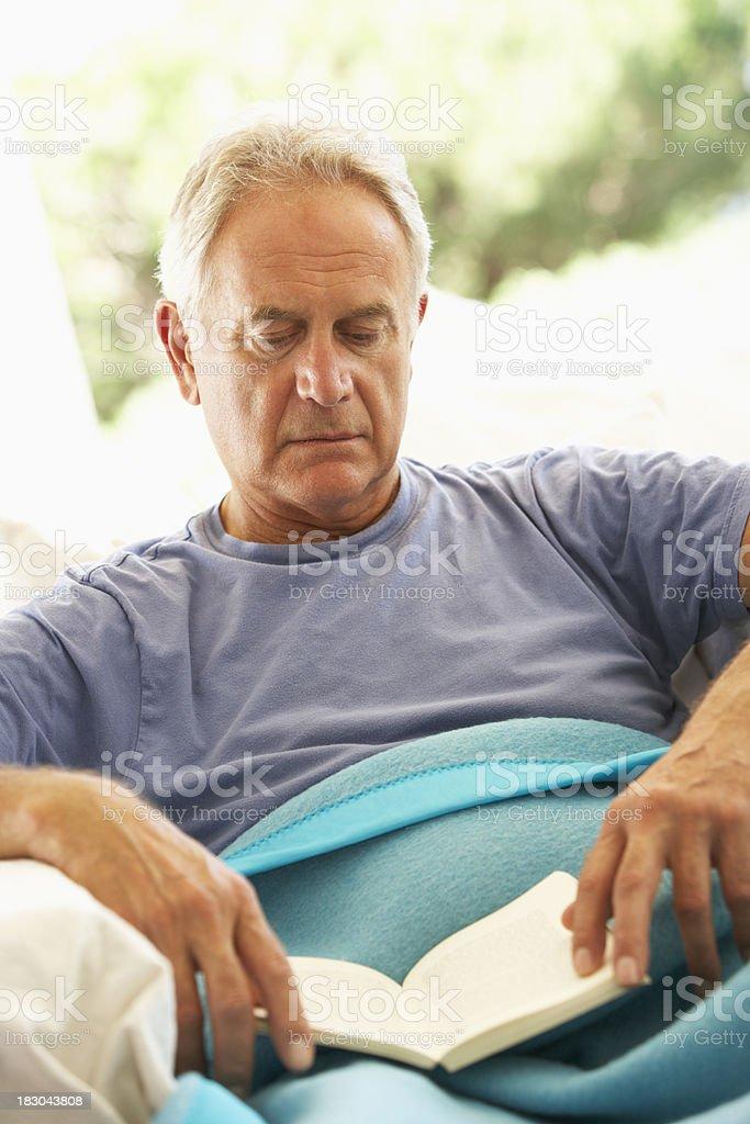 Senior Man Feeling Unwell Resting Under Blanket royalty-free stock photo