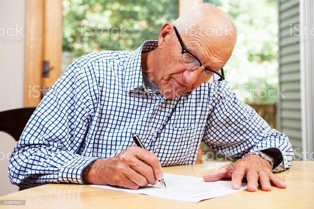 Senior Man Filling Out Paperwork, Signing Document stock photo