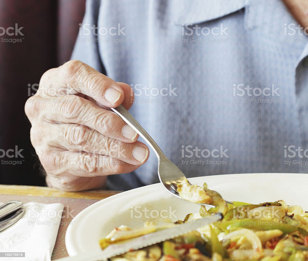 Senior Man Fingers Holding Breakfast Fork Close-Up stock photo