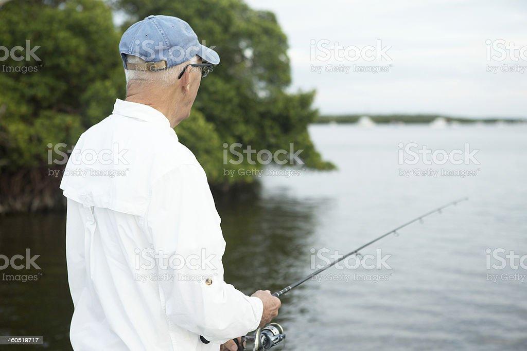 Senior Man Fishing near Mangroves on Intracoastal Waterway stock photo