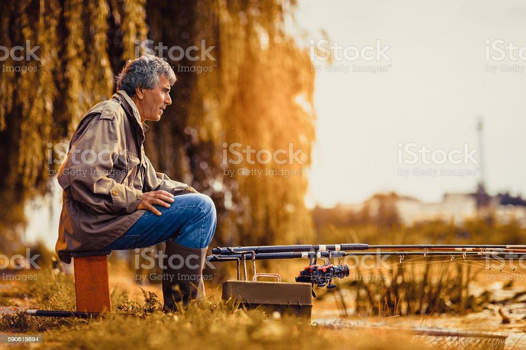 Senior man fishing on a freshwater lake sitting patiently stock photo