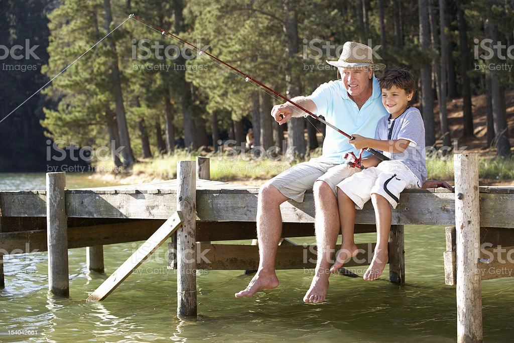 Senior man fishing with grandson royalty-free stock photo