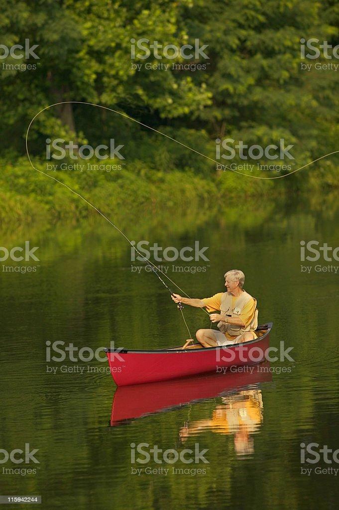 Senior Man Fly Fishing From Canoe royalty-free stock photo