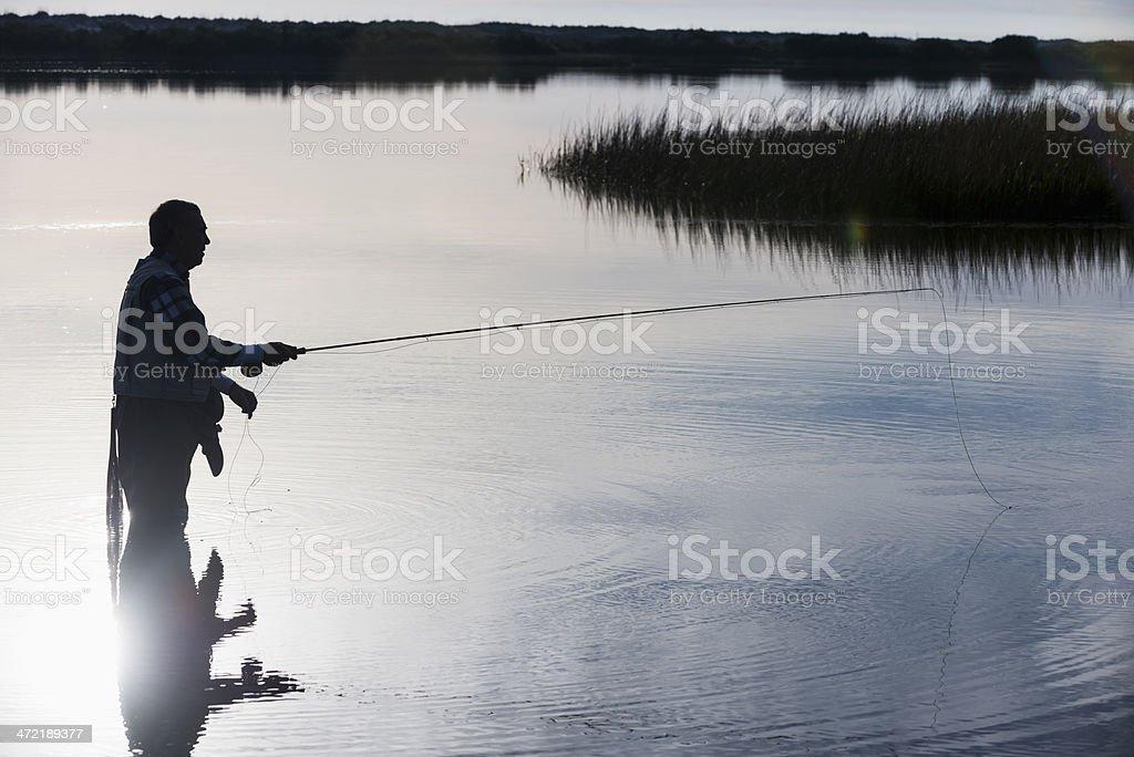 Senior man fly fishing stock photo
