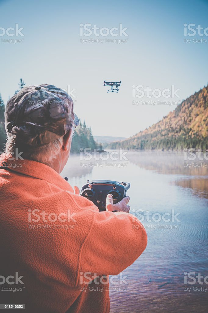 Senior Man Flying a Drone in Forest stock photo