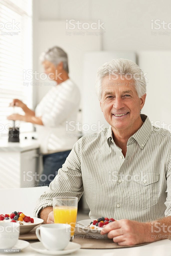 Senior man gaving breakfast with his wife at the back royalty-free stock photo