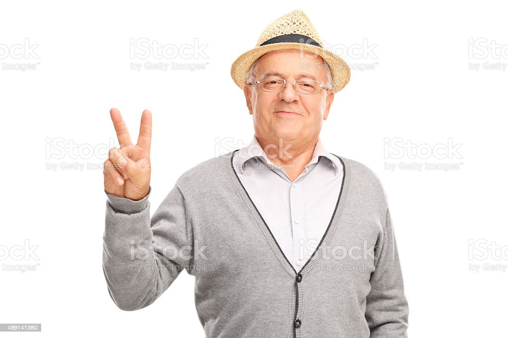 Senior man gesturing peace sign with his hand stock photo