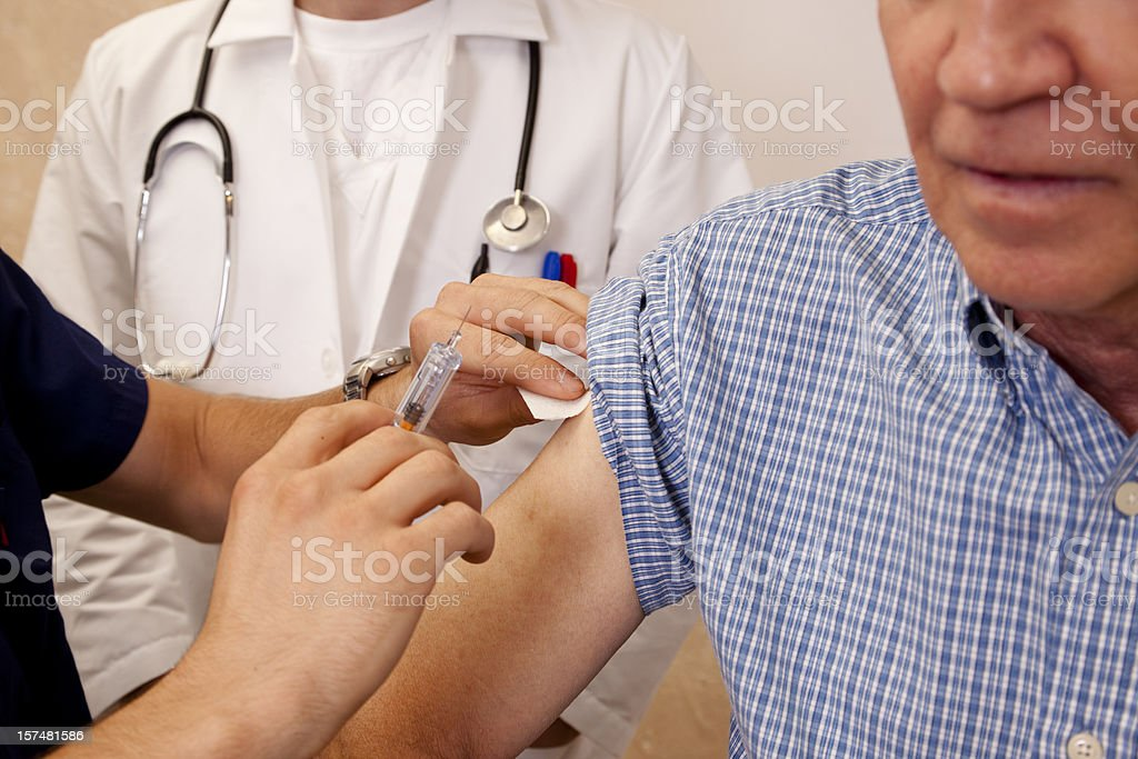 Senior man getting an injection from a nurse or doctor royalty-free stock photo