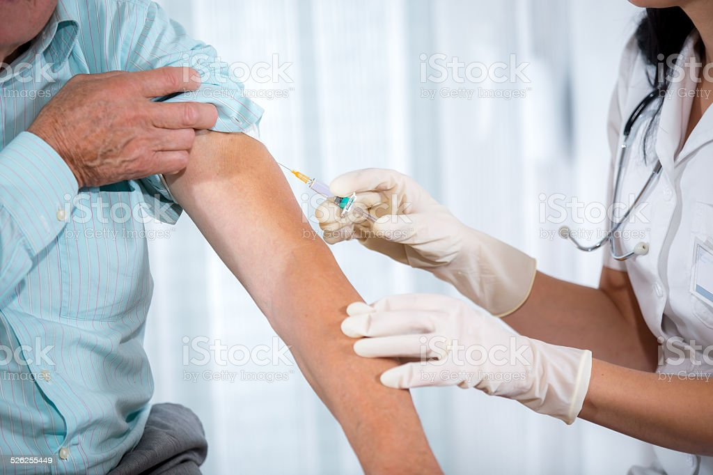 Senior man getting an injection stock photo