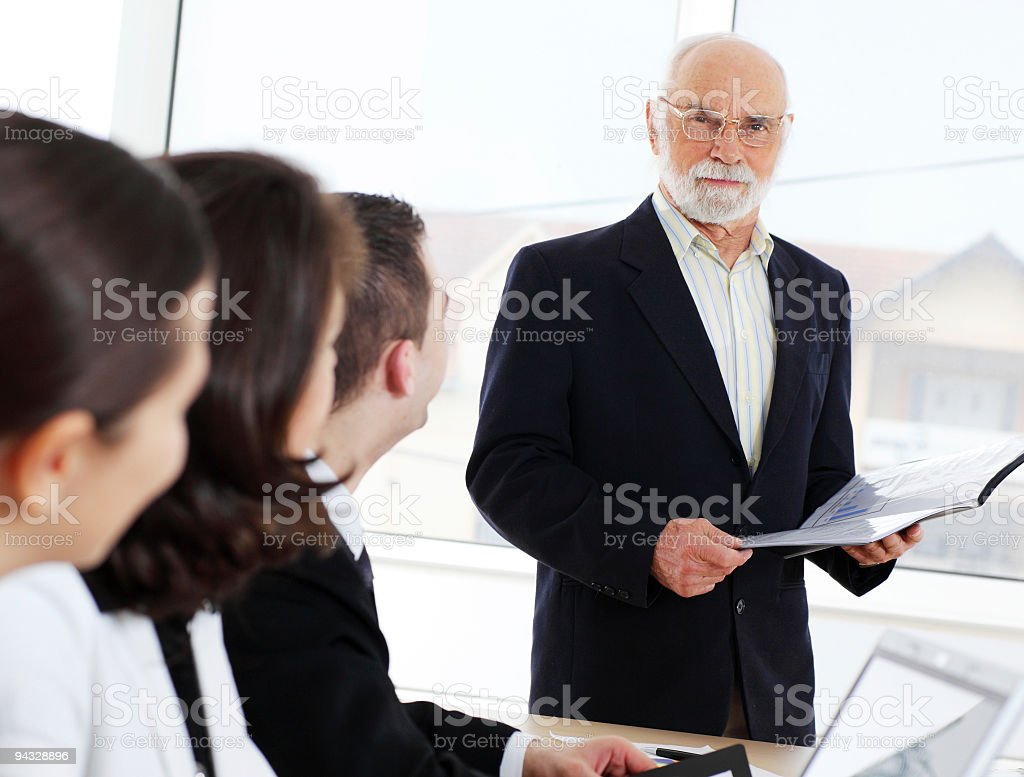 Senior man giving an explanation to colleagues. royalty-free stock photo