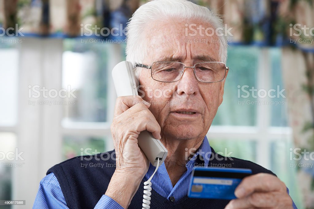 Senior Man Giving Credit Card Details On The Phone stock photo