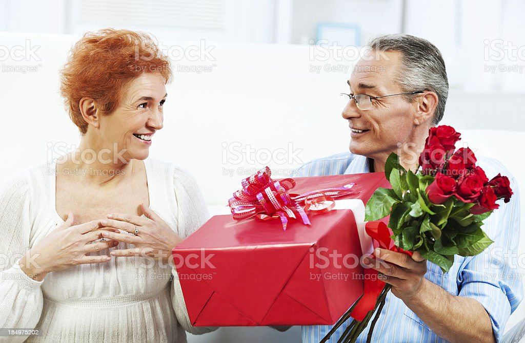 Senior man giving presents to his wife for Valentines Day. royalty-free stock photo