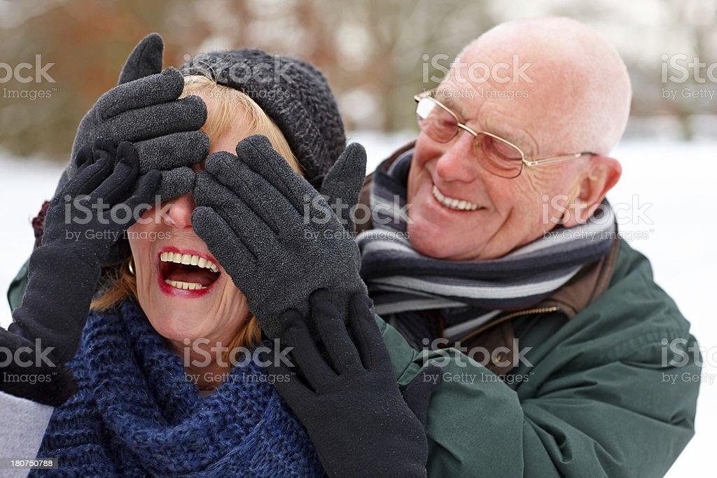 Senior man giving surprise to his wife stock photo