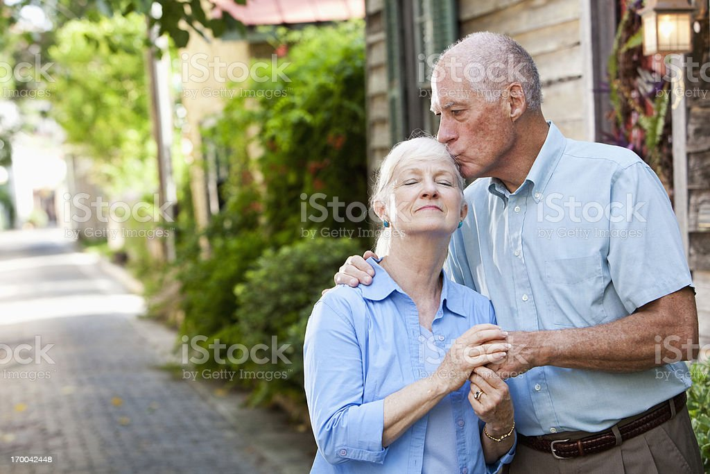 Senior man giving wife a kiss stock photo