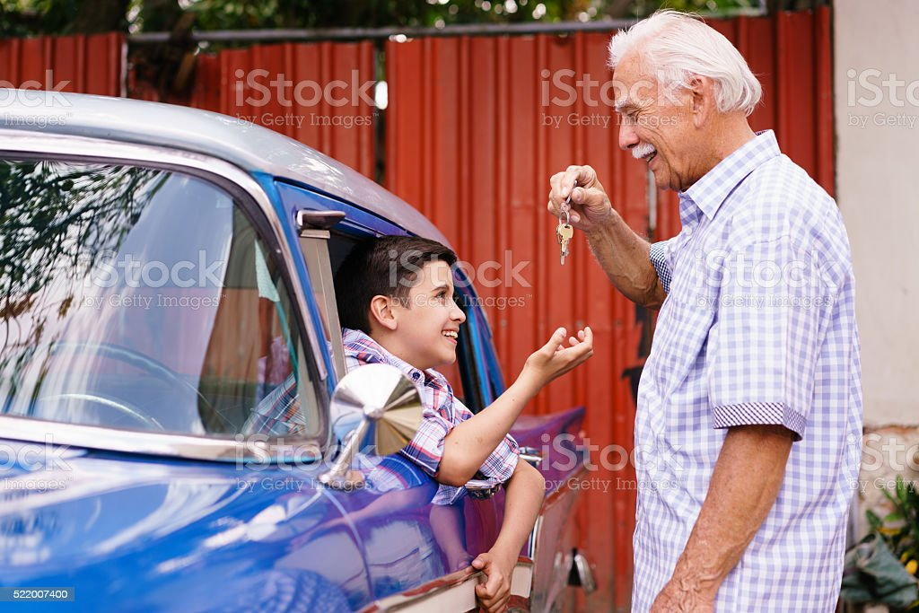 Senior Man Grandfather Giving Car Keys To Boy stock photo