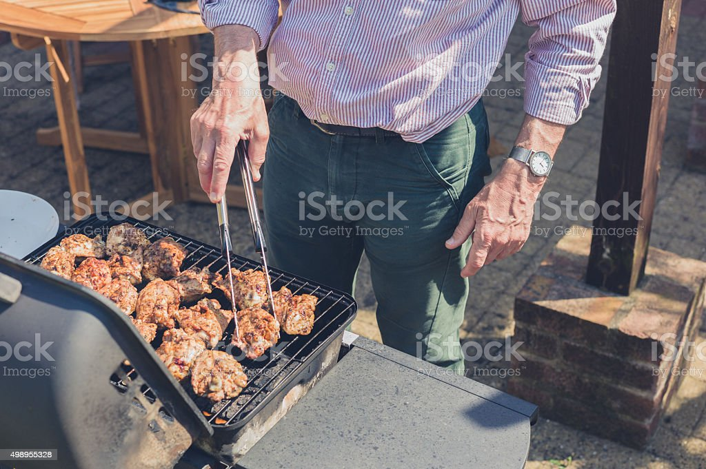 Senior man grilling meat on barbecue stock photo