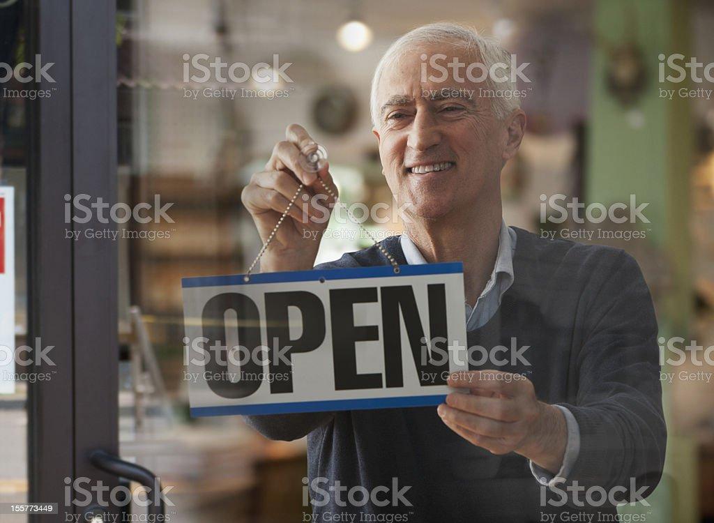 Senior man hanging open sign stock photo