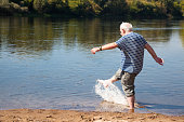 senior man has fun paddling and splashing in river