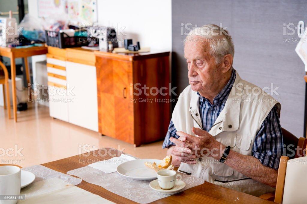 Senior Man Having Breakfast In Elderly Day Care Center stock photo