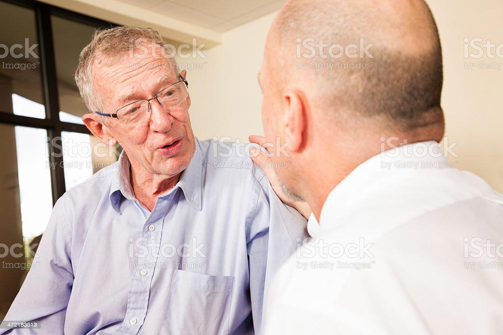 Senior man having conversation with caring mature man royalty-free stock photo