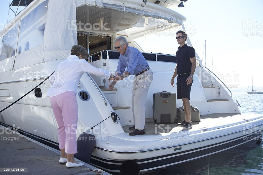 Senior man helping senior woman onto yacht, crew member in background royalty-free stock photo