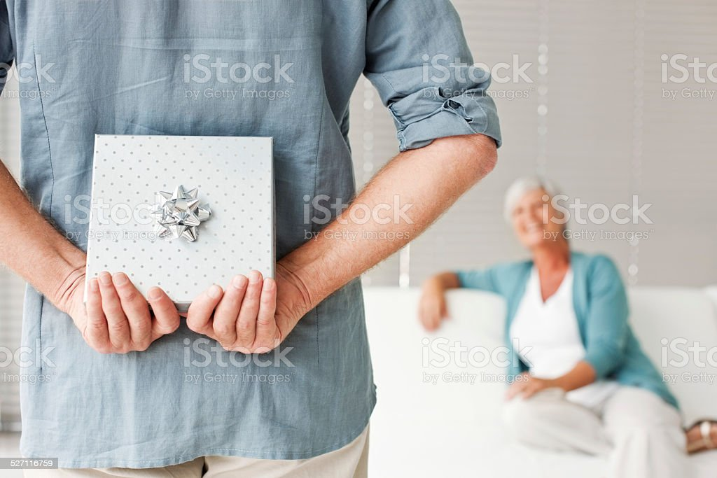 Senior Man Hiding Present In Front Of Woman stock photo