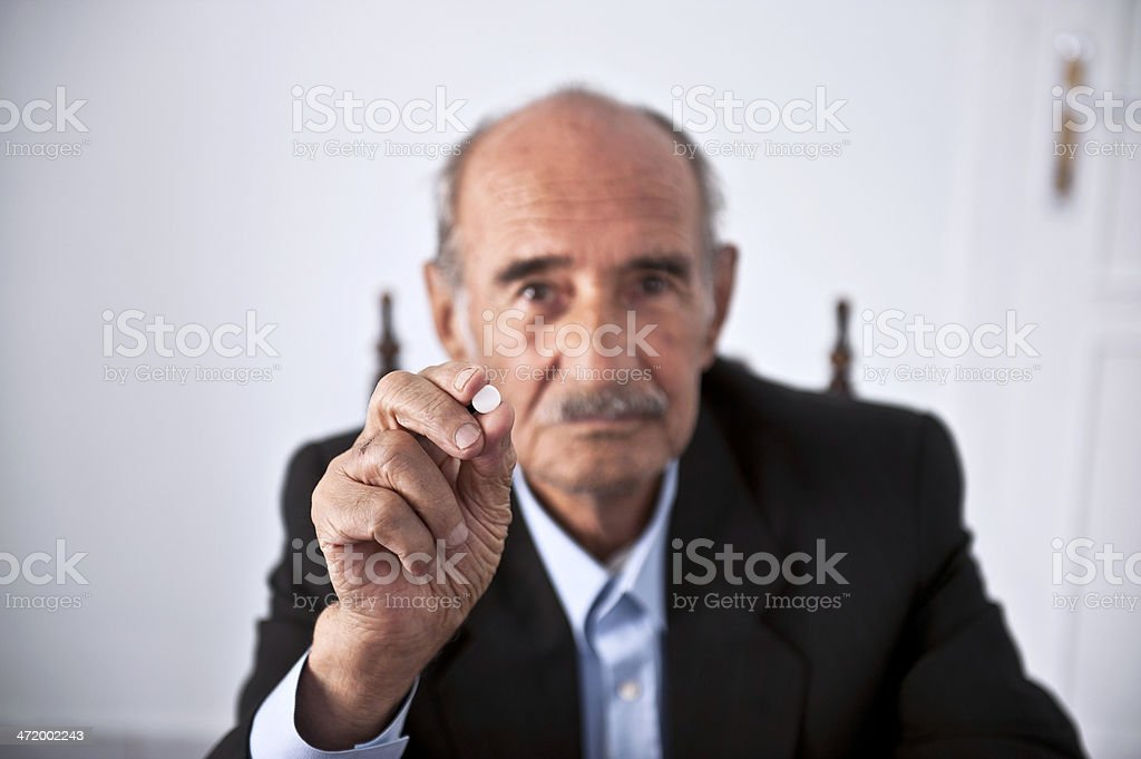 Senior man holding a pill royalty-free stock photo