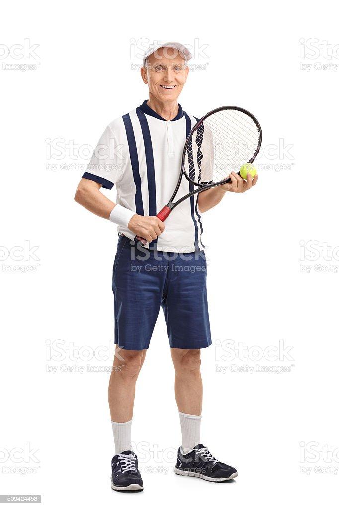 Senior man holding a racket and a tennis ball stock photo