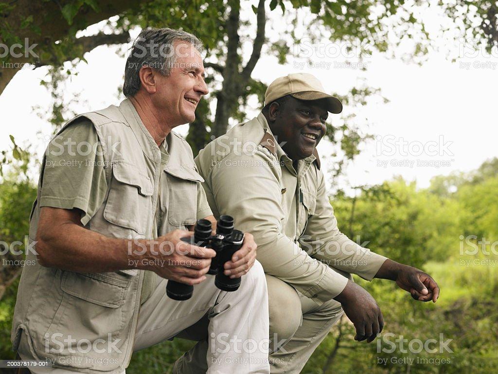 Senior man holding binoculars, on safari with guide, smiling royalty-free stock photo