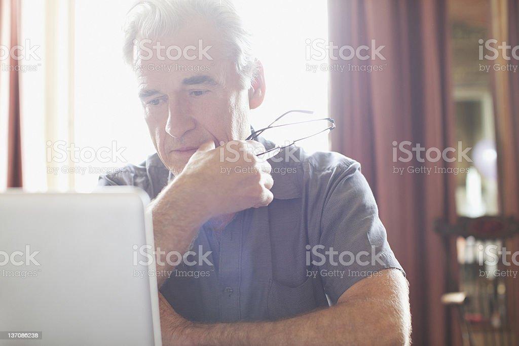 Senior man holding eyeglasses and using laptop stock photo