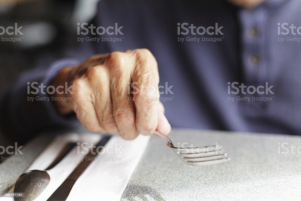 Senior Man Holding Fork at Restaurant Table stock photo