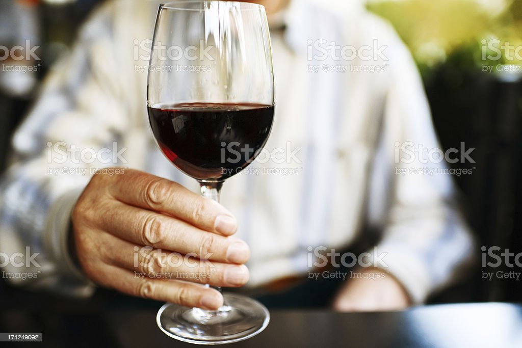 Senior Man Holding Glass of Red Wine in Outdoor cafe royalty-free stock photo