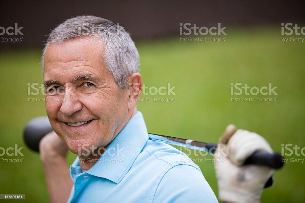 Senior man holding golf club behind his back stock photo
