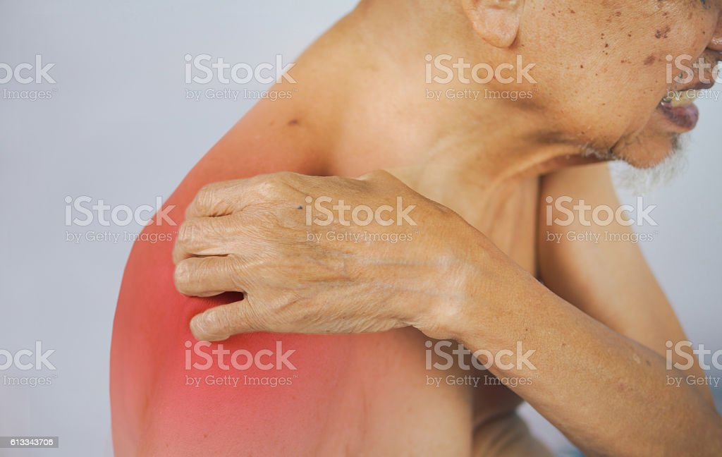 senior man holding he shoulder on pain area. stock photo