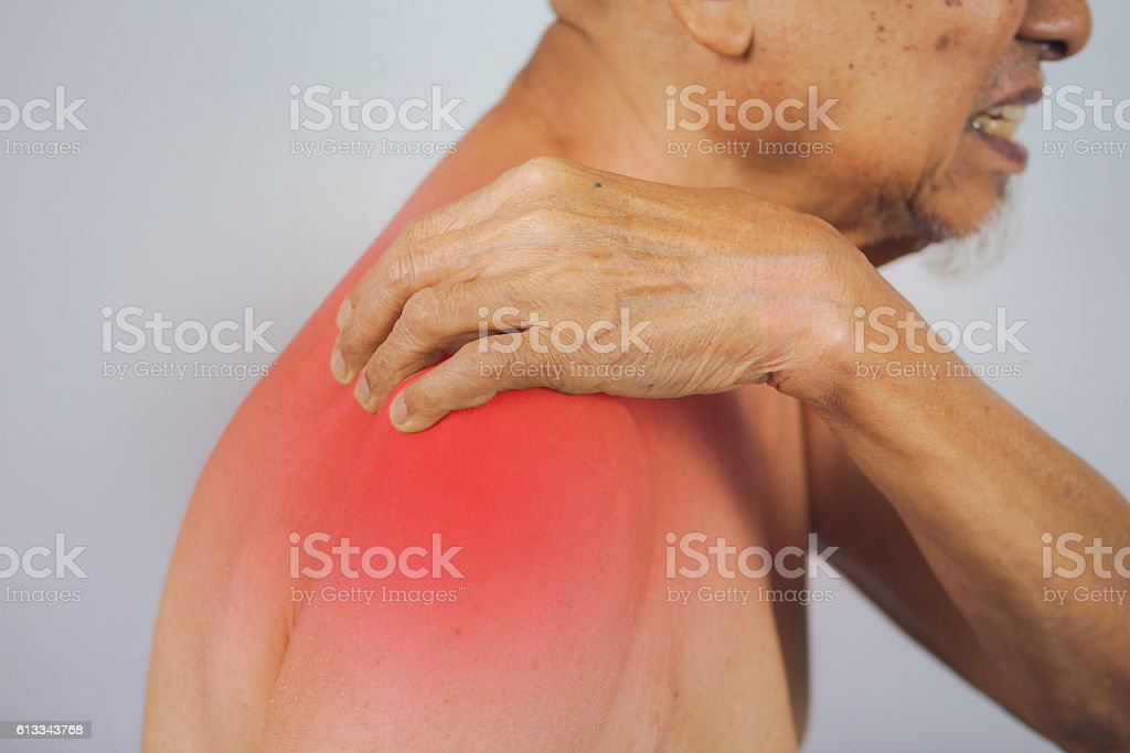 senior man holding he shoulder on pain area stock photo