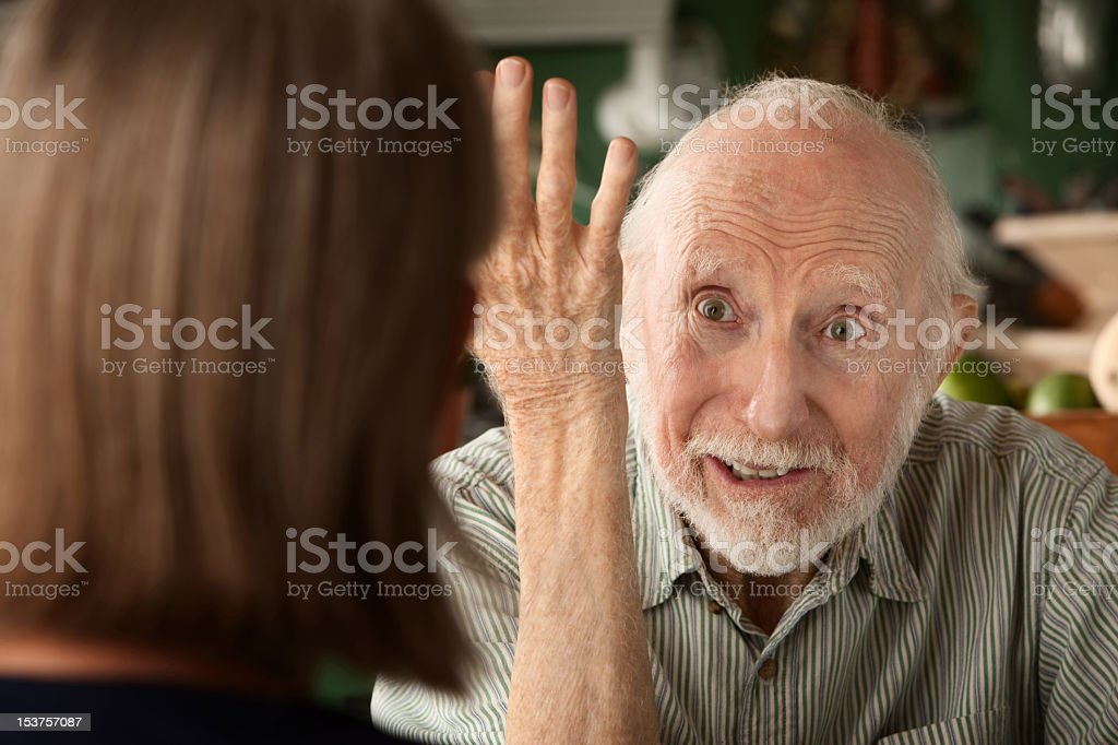 Senior man holding his arm up to woman facing him stock photo