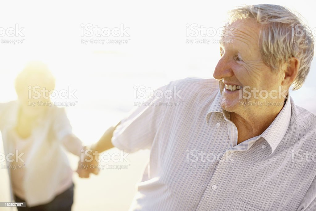 Senior man holding his wife's hand on the beach royalty-free stock photo