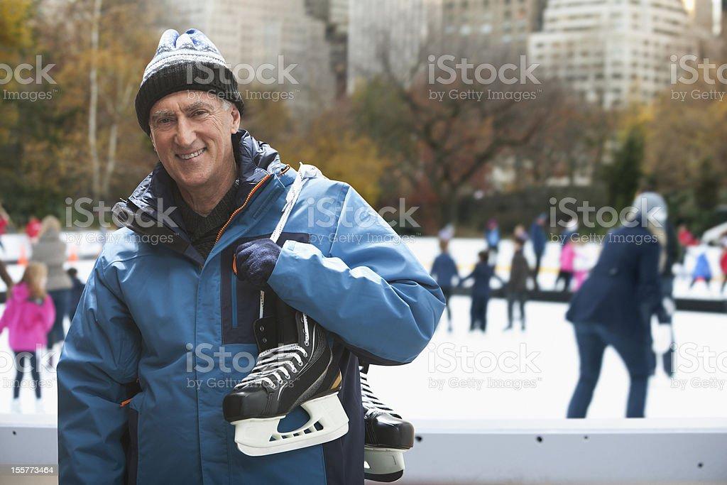 Senior man holding ice skates stock photo