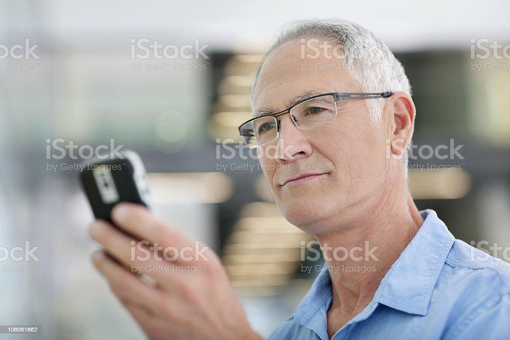 Senior man holding mobile phone royalty-free stock photo