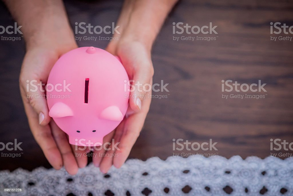 Senior man holding piggy bank at his home stock photo