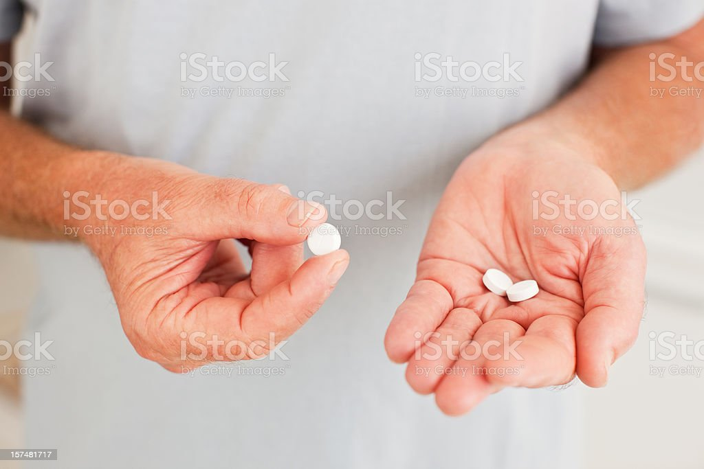Senior man holding pills royalty-free stock photo