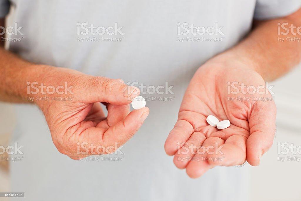 Senior man holding pills stock photo