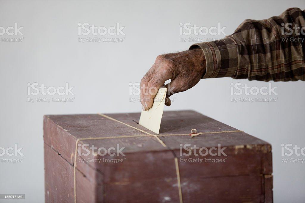 Senior Man Holding Poll Envelope On Locked Ballot Box royalty-free stock photo