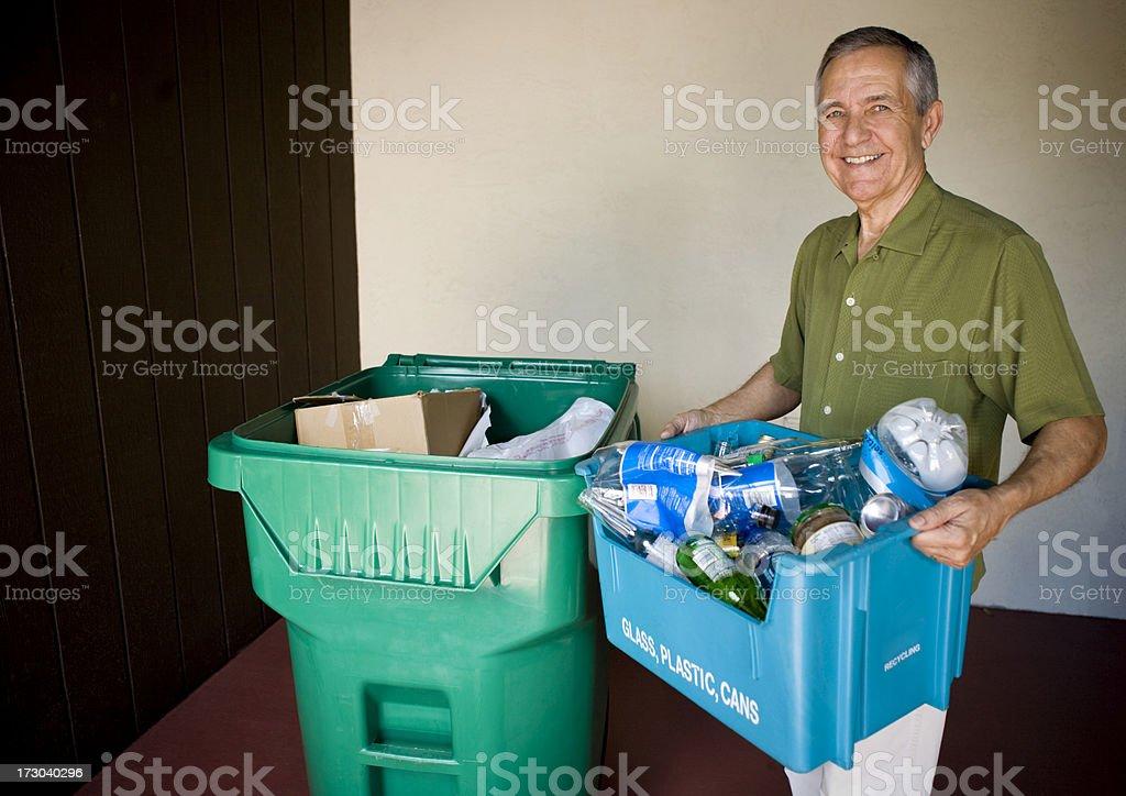 Senior man holding recycling bin with trash royalty-free stock photo