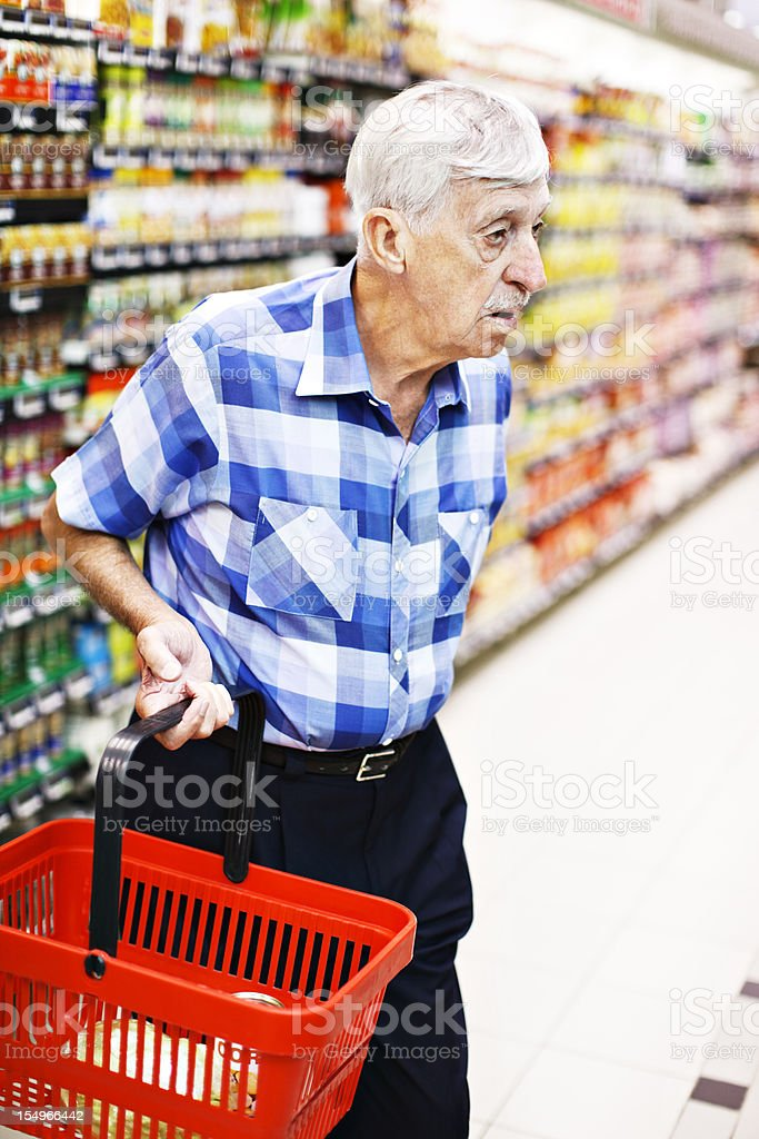 Senior man holding shopping basket seems confused in supermarket stock photo