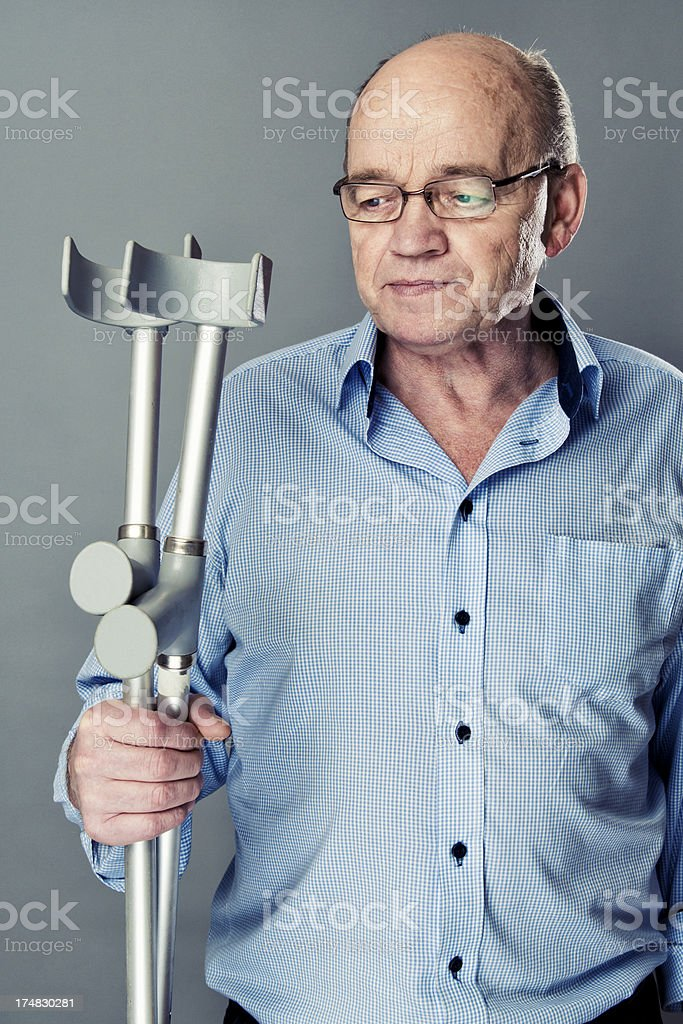 Senior man holds a pair of crutches and looks sad royalty-free stock photo