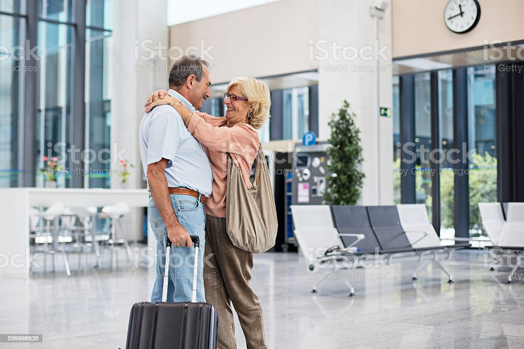 Senior man hugging his wife on arrival to airport stock photo