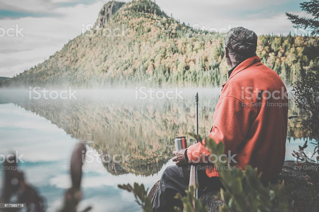 Senior Man Hunter Relaxing with Coffee in Nature stock photo