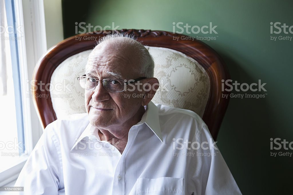 Senior man in a chair by the window stock photo